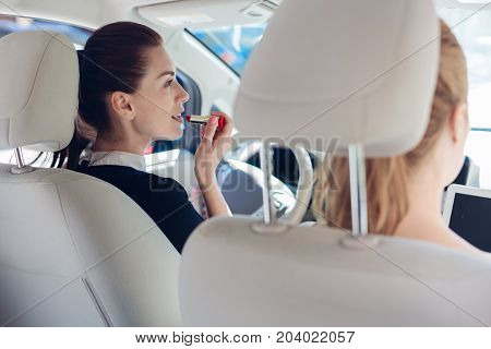 Looking great. Attractive nice pretty woman sitting behind the wheel and using a lipstick while looking into the mirror