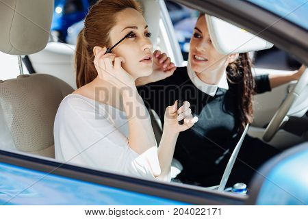 Magnetic look. Beautiful nice attractive businesswoman using mascara and painting her eyelashes while sitting in the car