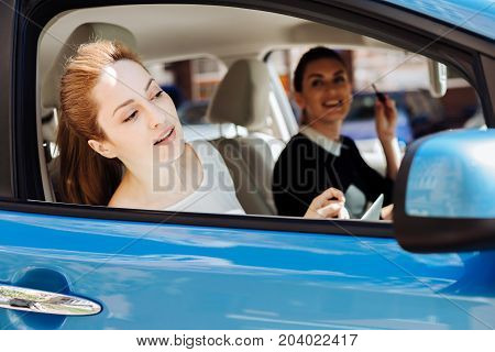 On the way to work. Attractive pleasant nice businesswoman sitting in the car with her colleague and looking out of the window while looking at the view