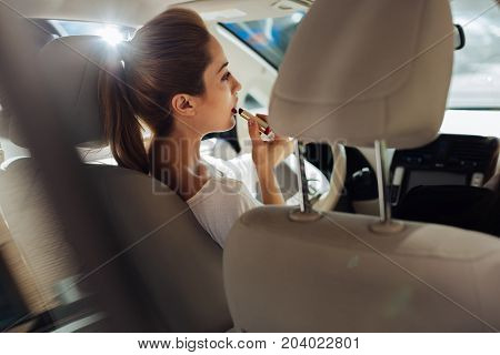 Dangerous multitasking. Attractive pretty young woman sitting behind the wheel and driving her car while putting on makeup