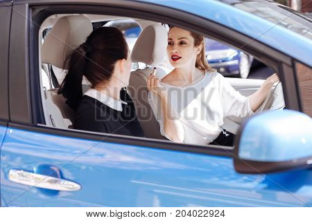 How do I look. Positive nice attractive businesswoman holding a lipstick and looking at her colleague while asking her opinion about the look