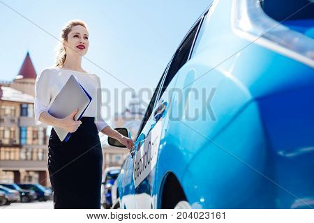 To the office. Pleasant smart nice businesswoman smiling and opening her car while being ready to go to the office