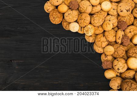 Cookies background. Sweet chocolate chips biscuits heap at black rustic wood background with copy space. Oatmeal, chocolated drops and other sweets. Fattening dessert for tea on wooden table top view