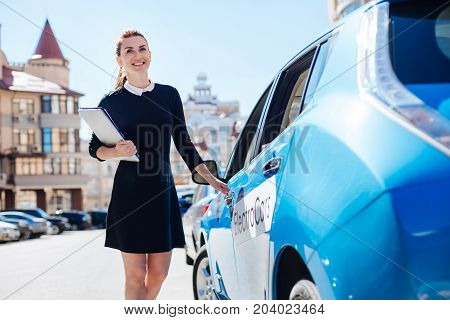 Ready to work. Joyful positive happy businesswoman holding documents and smiling while opening her car