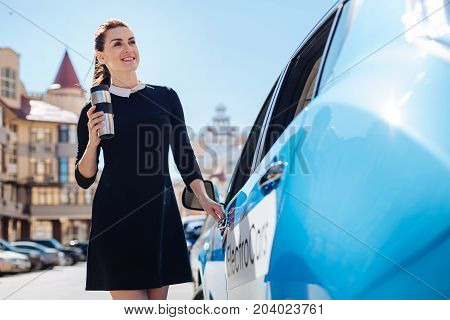 Successful businesswoman. Happy pleasant attractive woman standing near her car and opening it while holding a thermo cup