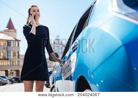 Professional businesswoman. Delighted nice attractive businesswoman talking on the phone and smiling while opening her car