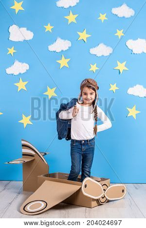 Little child girl in a pilot's costume is playing and dreaming of flying over the clouds. Portrait of funny kid on a background of bright blue wall with yellow stars and white clouds