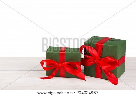 Group of gift boxes wrapped with green paper and red satin ribbon on wood at white background. Modern presents for any holiday, christmas, valentine or birthday