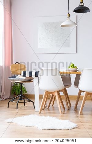 Fur on wooden floor in cozy dining room with silver painting and dining table with white chairs