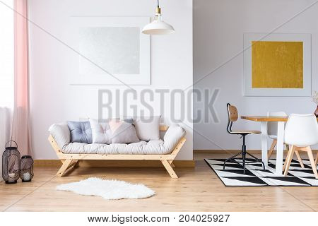 Gold and silver gallery in spacious room with pastel pillows on sofa and dining table on black and white carpet