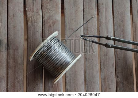 Soldering irons and lead on bamboo background