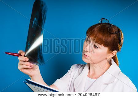 Pensive doctor dentist looks at x-ray shot of jaw, holds pen in hand