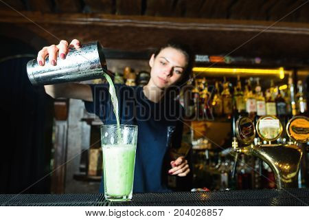 Barmen cakes a cocktail at the bar. A bartender girl pours a shaker ingredient into a glass of cocktail