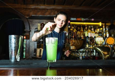 A bartender girl creates a beautiful green cocktail in a nightclub. The barman squeezes lime juice into an alcoholic cocktail.