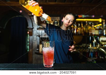 The girl bartender creates a delicious alcoholic cocktail at the nightclub. The barman pours syrup into an alcoholic cocktail