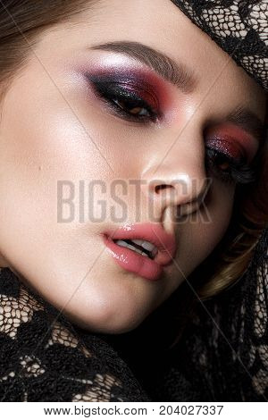 Close up portrait of beautiful young woman with evening makeup and wavy hairstyle. Purple smoky eyes