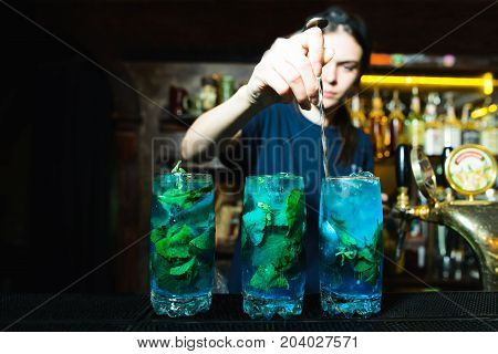 The barman mixes the ingredients in a bright alcoholic cocktail. The girl bartender makes a nice blue liquor in the bar.