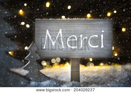 Sign With French Text Merci Means Thank You. White Christmas Tree With Snow And Magic Glowing Lights In Backround And Snowflakes. Card For Seasons Greetings.