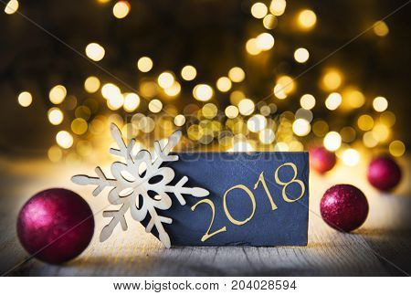Plate With Golden Text 2018 For Happy New Year Greetings. Bright Glowing Lights In The Background. Christmas Ornament Like Red Balls And Snowflake.