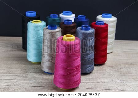Group of bobbins of thread of various colors on a wooden table