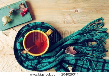 Autumn background - cup of tea, old book and warm scarf on the wooden background. Autumn still life. Still life with autumn concept of spending autumn time at cozy home. Autumn composition. Vintage autumn background. Autumn at home