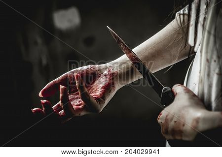 Asian girl dress killer to Halloween festival She's holding a kitchen knife and a big soaked with blood with terrible eyes. She took a kitchen knife at her arm and acting like trying to suicide