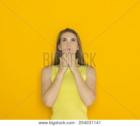 Excited young attractive woman. Funny impatient emotional girl. Studio shot orange background