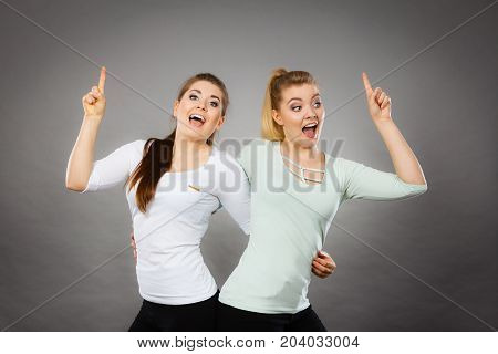Gestures having idea concept. Happy two women pointing up with finger. Studio shot on light dark background