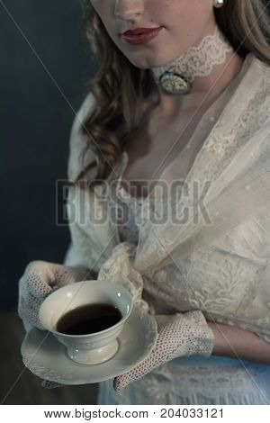 Hands Of Victorian Girl Holding Cup Of Tea.