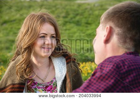 Young couple on a picnic in a beautiful place under the open sky. Sitting on a plaid, the girl looks at her lover against the background of green meadows