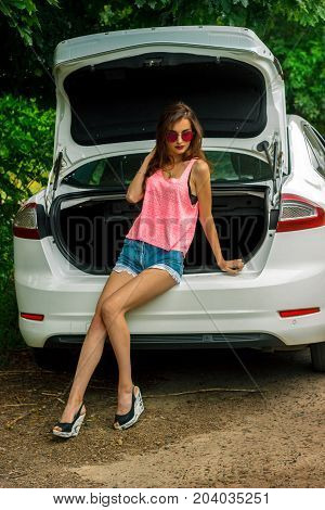 fashionable slim girl in shorts and a bright shirt sits in the trunk of a car