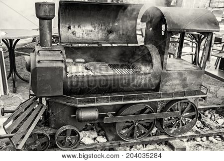 Barbecue grill with meat in shape of old steam locomotive. Bbq scene. Garden reastaurant. Black and white photo.