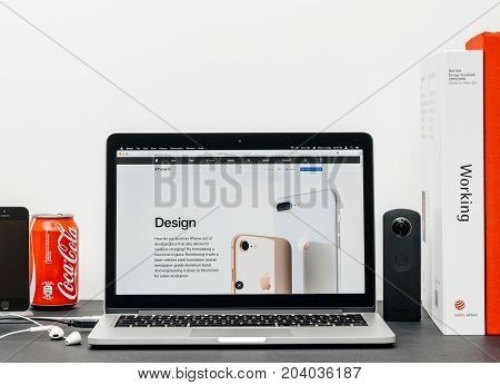 PARIS FRANCE - SEP 13 2017: Minimalist creative room table with Safari Browser open on MacPook Pro laptop showcasing Apple Computers website with latest iPhone 8 and 8 Plus with updated desgin