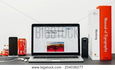 PARIS FRANCE - SEP 13 2017: Minimalist creative room table with Safari Browser open on MacBook Pro laptop showcasing Apple Computers website with latest iPhone 8 and 8 Plus with best color accuracy