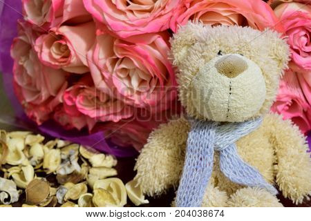 Teddy bear sits with a bouquet of roses