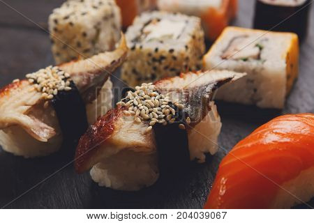 Sushi and rolls closeup. Japanese restaurant delivery. Salmon, unagi, california and other healthy meals on dark wooden background