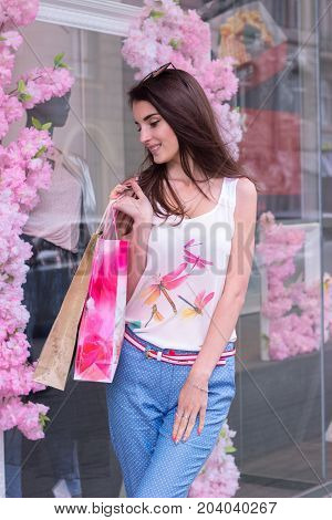 gentle smiling girl holding a packages of stores