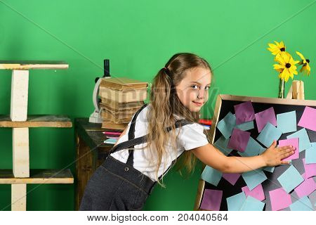 Girl With Ponytails Puts Sticky Notes On Blackboard Near Flowers