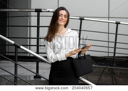 charming young girl in white shirt smiling keeps the bag and looks at the camera