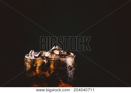 Close up iced cola glass. Sparkling water soft drinks in glass with ice on dark background.