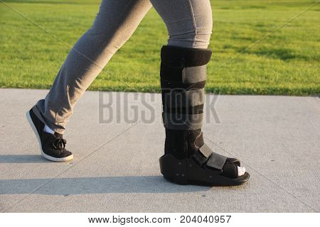 Walking with a broken leg immobilized with walking cast boot