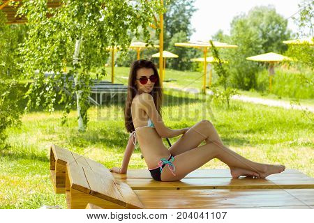 Slim young girl in a bathing suit on a beach Lounger is looking at the camera