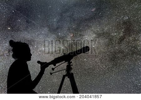 Woman looking at the stars with telescope beside her