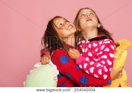 Girls In Colorful Pajamas Hold Funny Bright Pillows