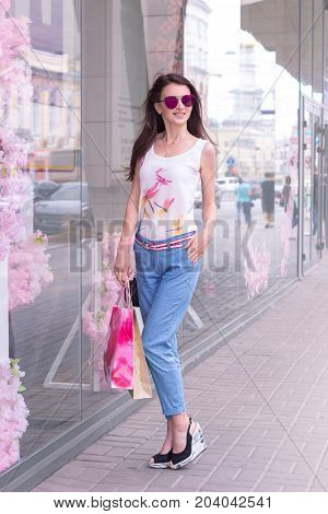 young fashionable lady in mirrored sunglasses and slacks standing on the street with packages