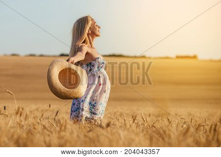 A young pregnant woman in a wheat field Concept photo of pregnancy pregnant woman newborn and baby.