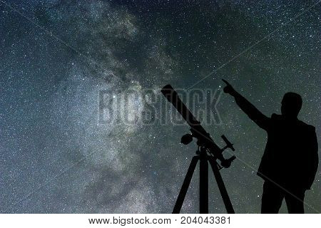 Milky Way. Night sky with stars and silhouette of a standing man with telescope.