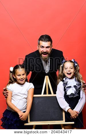 Girls and man with happy faces. Bearded teacher and kids wearing school clothes lean on blackboard copy space. Schoolgirls near board and tutor on red background. Back to school and classroom concept