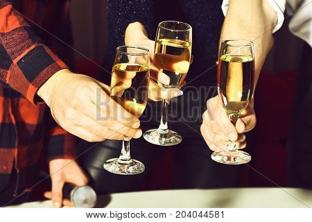Three glasses with wine or champagne cheers in female and male hands clinking at party in cafe or bar on white curtain