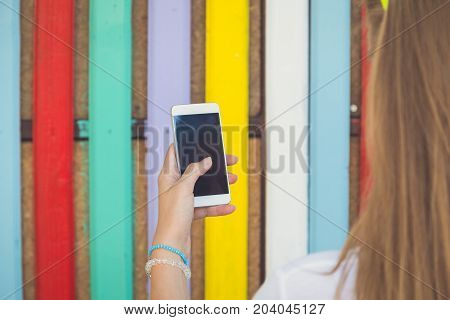Close up of female hand holding blank screen smartphone. Wooden colorful fence in the background.